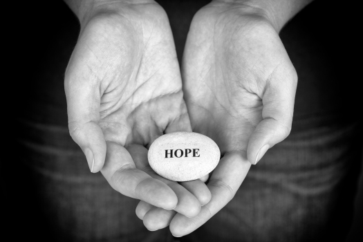 Stone with the word Hope in the woman's palms